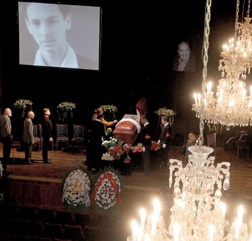 На огромном мониторе, установленном над гробом, показывали фотографии из личного архива покойного