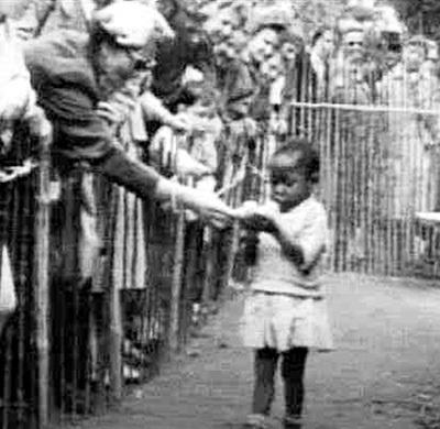 Бельгия, 1958 год. Африканскую девочку показывают в зоопарке. От посетителей отбоя нет, они несут ребёнку бананы, как обезьянке