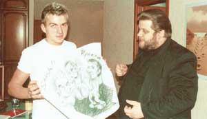 С МИХАИЛОМ ФИЛИМОНОВЫМ: Влад демонстрирует музыкальному обозревателю «ЭГ» плакат, где аллегорически изображена его битва с певцом Иракли на МТV
